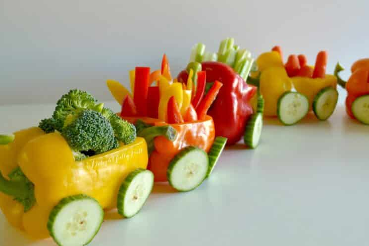 bell peppers hollowed out to look like train cars carrying veggie sticks