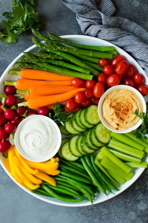 White platter with assorted veggies and different dips in white bowls
