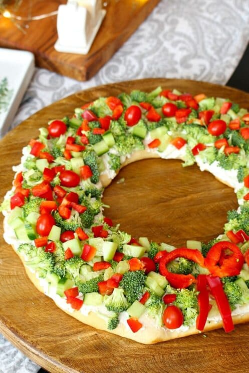 Pizza shaped in a wreath topped with broccoli, peppers and cucumbers