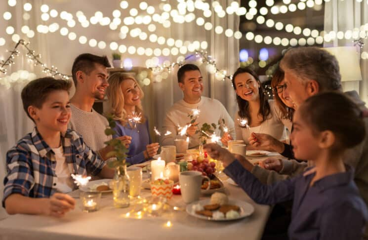 children and adults sitting around a table eating appetizers and holding sparklers with lights in the background