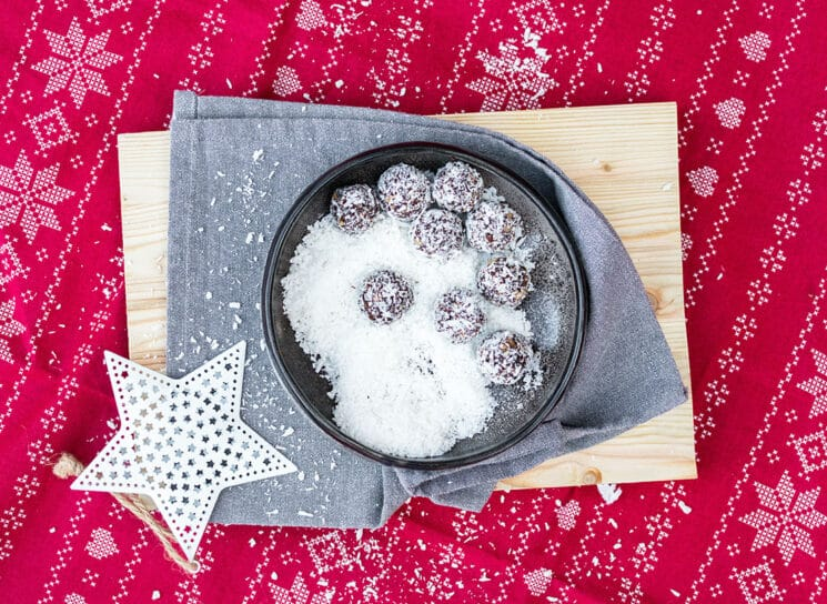 no bake snowball energy balls for santa in a bowl with coconut on top a wood board with a white star and a red christmas cloth