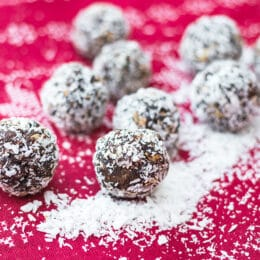 no bake snowball energy balls with coconut on a festive red christmas cloth and extra coconut scattered
