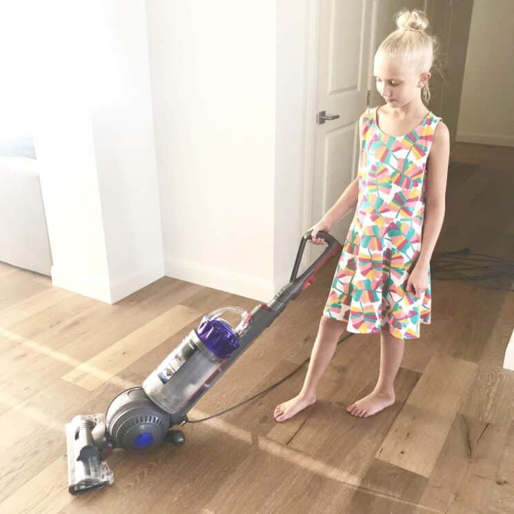 A young girl vacuuming
