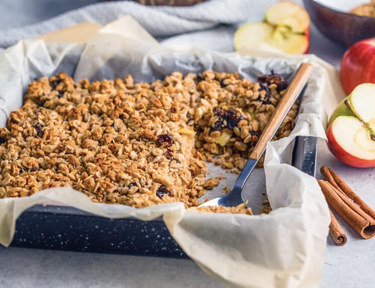 apple cinnamon baked oatmeal in a square pan with parchment paper