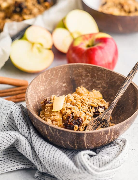 Apple cinnamon baked oatmeal in wooden bowl with a spoon