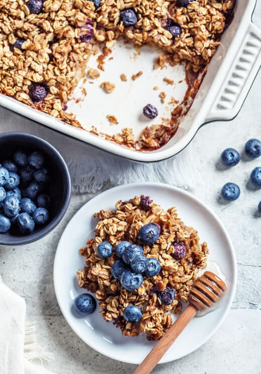 Baked oatmeal with blueberries and honey on a white plate. Baked Blueberry Oatmeal
