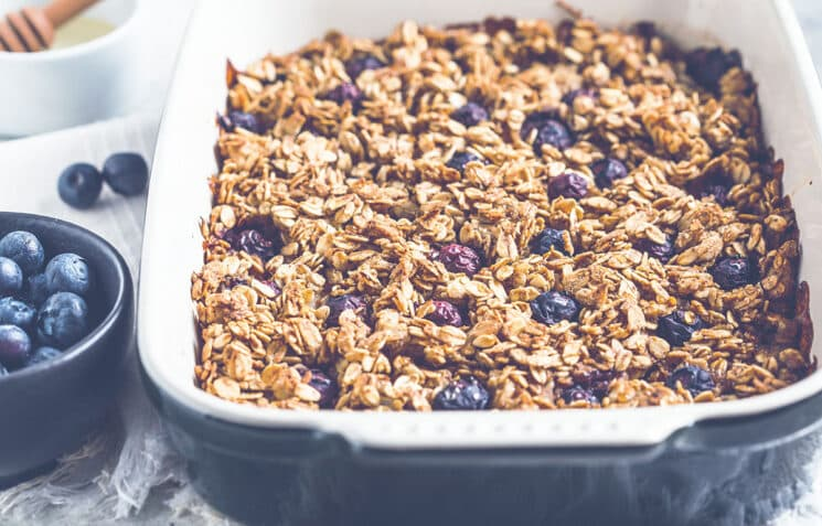 Baked oatmeal with blueberries and honey in the oven dish.