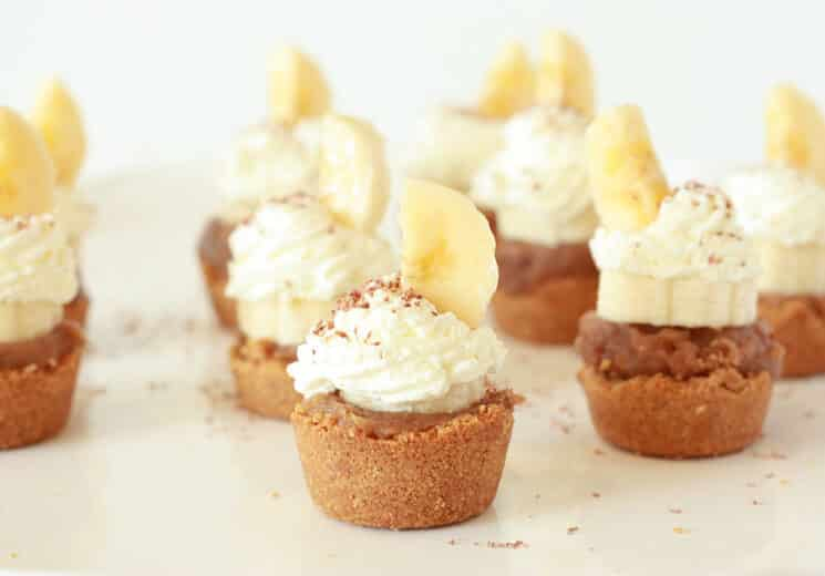 banoffee pie bites with whip cream and a sliced banana on top on a white plate