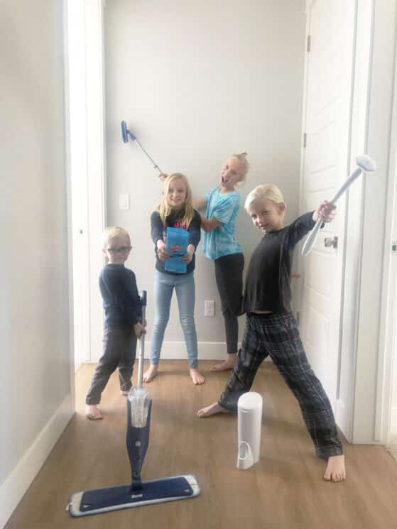 a group of young kids holding cleaning appliances