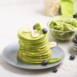 Green pancakes with spinach and blueberries, healthy snack, vegetarian food