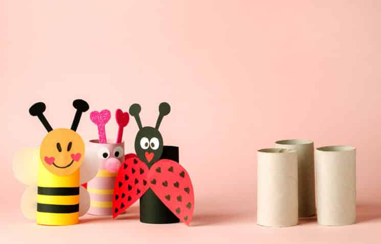 Paper toy insect for valentine romance baby shower, birthday party. Easy crafts for kids on pink background, copy space, die creative idea from toilet tube roll, recycle reuse eco