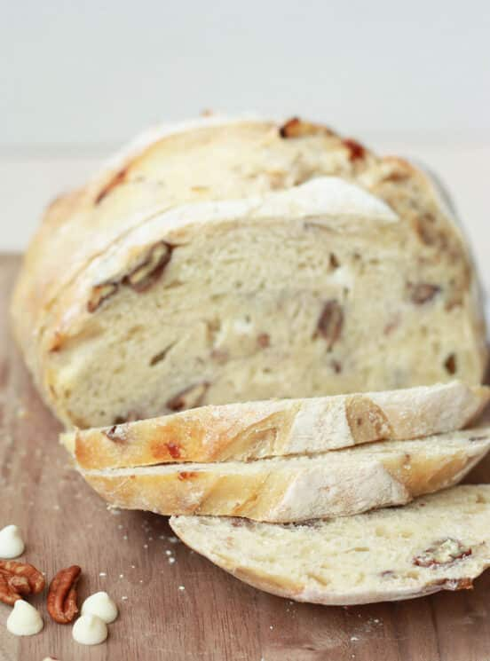 white chocolate pecan sourdough bread sliced on a wood cutting board