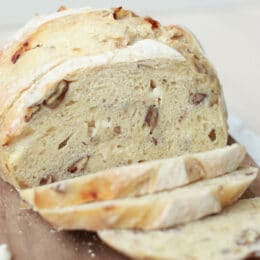 white chocolate pecan sourdough bread sliced on a wooden cutting board