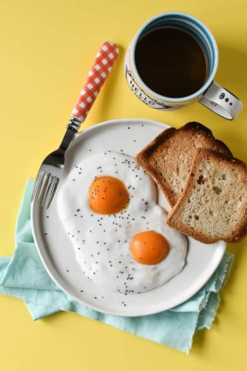 yogurt and apricot halves designed to look like a sunny up egg on a yellow background with a mug of juice