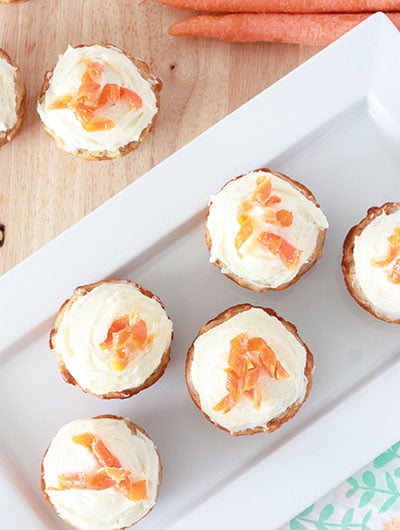 overhead view of carrot cake muffins on a wood surface with carrot curls