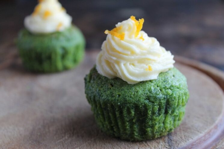 green kale cupcakes topped with a swirl of white frosting and orange zest on a wooden plate
