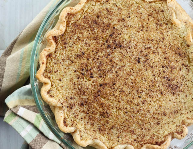 a whole pie topped with cinnamon in a glass pie pan set on a plaid dish towel