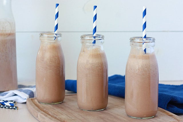 homemade chocolate milk in milk bottles with blue and white striped straws