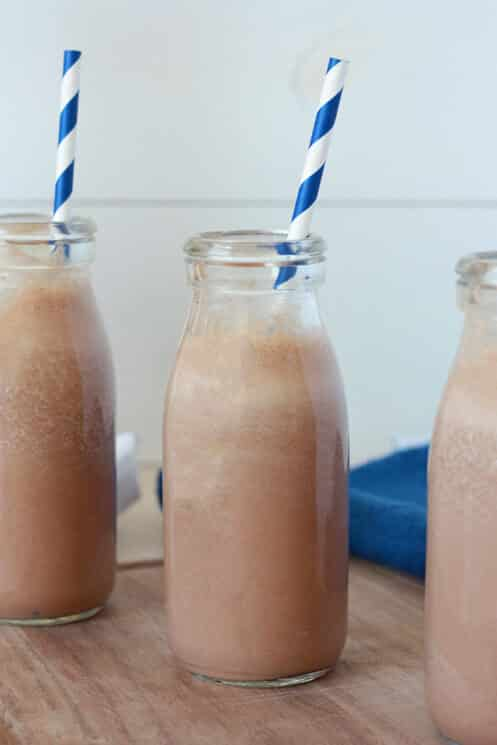 Close up of a milk bottle with chocolate milk and blue and white striped straw