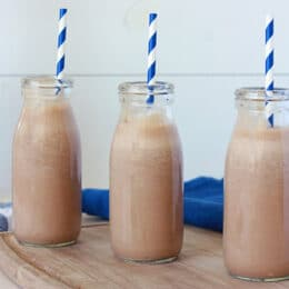 3 milk bottles of chocolate milk with blue and white striped straws