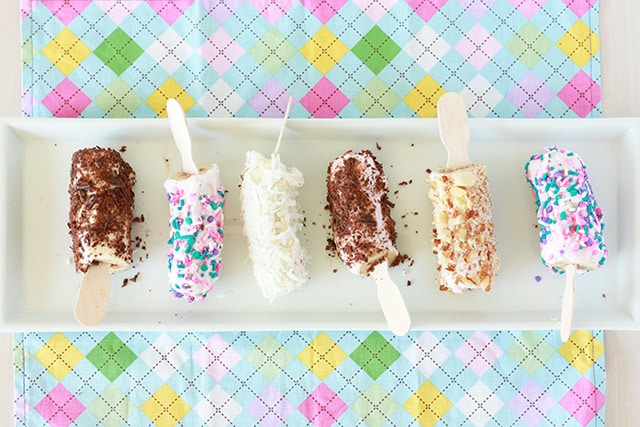 Frozen bananas pop on a white tray with different toppings: sprinkles, coconut, chocolate pieces, nuts