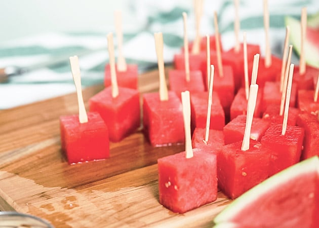 Watermelon cubes on a wooden cutting board with popsicles