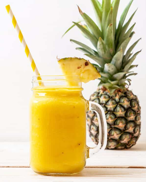 pineapple cooler in a glass jar with a handle with a striped straw and a pineapple in the background