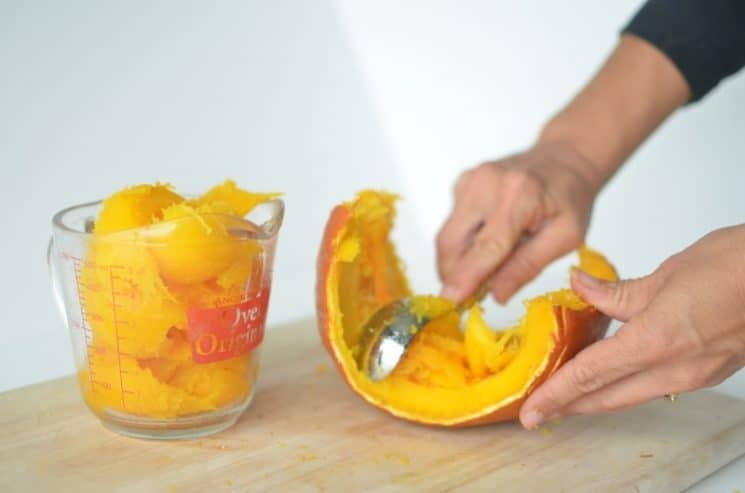 someone scooping pumpkin from it's shell into a glass container.
