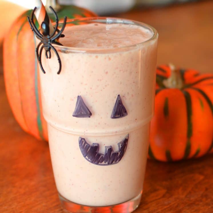 orange smoothie in a glass with a jack-o-lantern face drawn on
